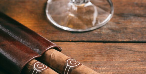 Cuban cigars and snifter with rum on wooden table